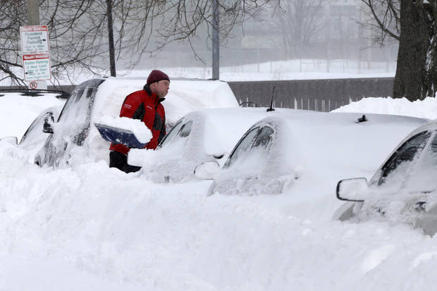 A man shovels snow off his car on M street in the South Boston neighborhood of Boston Saturday, Feb. 9, 2013 in Boston. Boston was blanketed in up to 2 feet of snow, falling short of the city's record of 27.6 inches set in 2003. In some communities just outside the city, totals were higher, including 30 inches in Quincy and Framingham. (AP Photo/Gene J. Puskar) ORG XMIT: MAGP225
