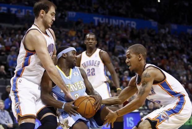 Nenad Krstic (left) and Eric Maynor grab at the ball held by Denver's Ty Lawson as Thunder teammate Jeff Green looks on in OKC's 114-106 victory on Christmas 2010. None of those three players remain with the Thunder, but OKC's Christmas tradition continues. (AP Photo)