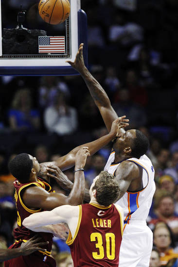 Oklahoma City Thunder center Kendrick Perkins, right, shoots over Cleveland Cavaliers forward Tristan Thompson, left, in the second quarter of an NBA basketball game in Oklahoma City, Sunday, Nov. 11, 2012. Cavaliers forward Jon Leuer (30) watches at center. (AP Photo/Sue Ogrocki)
