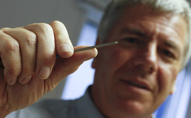 Garry Harvey, the official engraver of the Royal and Ancient Golf Club, holds up an engraving tool during the British Open Golf Championship at Muirfield, Scotland, Saturday July 20, 2013. (AP Photo/Alastair Grant)