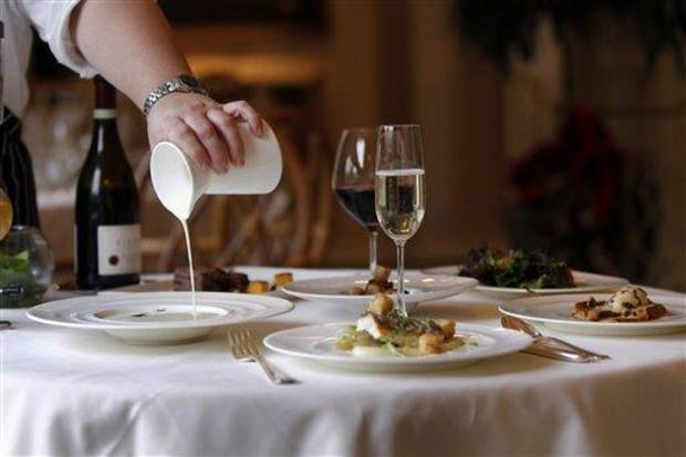 In this Dec. 7, 2012 photo, executive chef Kristin Butterworth pours roasted onion soup with onions as part of their reveillon menu at the Grill Room of the Windsor Court Hotel in New Orleans. Roughly 50 restaurants in New Orleans are reviving an old Creole custom called reveillon, which stems from the old French tradition of eating a lavish meal after midnight Mass on Christmas Eve. (AP Photo/Gerald Herbert)