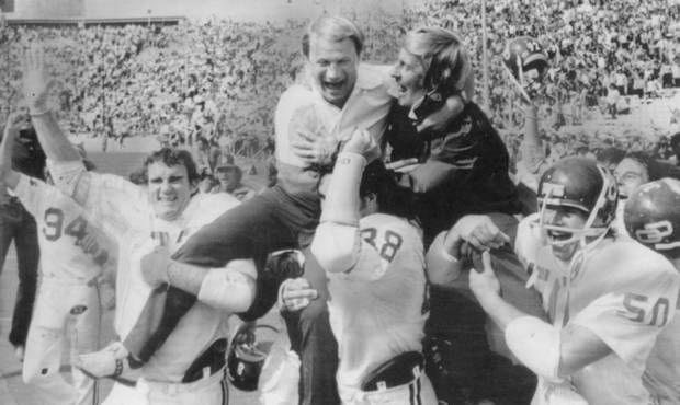OU football coach Barry Switzer and offensive line coach Gene Hochevar are carried off the field of the Cotton Bowl on 10-14-73.