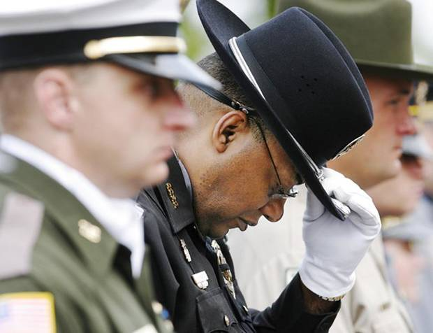 Oklahoma County Sheriff's Deputy  Leroy Scott touches the brim of his hat as he lowers his head while standing among honor guards from police departments throughout the state.at the 41st annual Oklahoma Law Enforcement Officers' Memorial Service on the grounds of the Department of Public Safety offices at NE 36 and MLK, Friday morning, May 8, 2009.    Photo by JIM BECKEL, THE OKLAHOMAN ORG XMIT: KOD