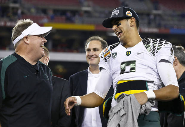 Oregon head coach Chip Kelly, left, laughs with Marcus Mariota after the Fiesta Bowl NCAA college football game against Kansas State Thursday, Jan. 3, 2013, in Glendale, Ariz.  Oregon defeated Kansas State 35-17.(AP Photo/Ross D. Franklin)