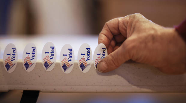 Poll worker Leon Levy attaches stickers to a tabletop on election day on Tuesday, Nov. 6, 2012, in Nashville, Tenn. After a grinding presidential campaign President Barack Obama and Republican presidential candidate, former Massachusetts Gov. Mitt Romney, yield center stage to American voters Tuesday for an Election Day choice that will frame the contours of government and the nation for years to come. (AP Photo/Mark Humphrey)