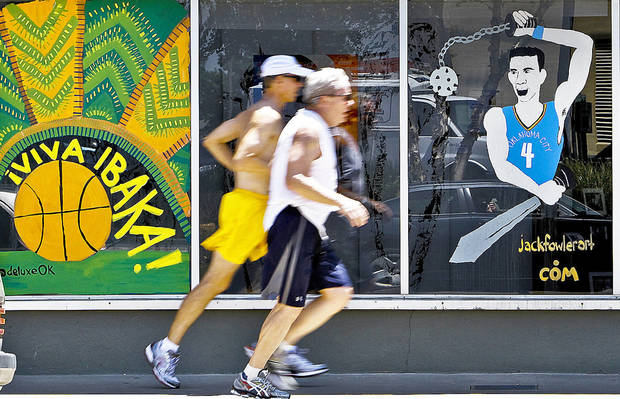Joggers run Monday on a sidewalk outside the IVC Gallery, which is decorated to support the Oklahoma City Thunder.  Photo by Chris Landsberger, The Oklahoman