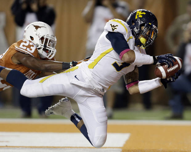 West Virginia's Stedman Bailey (3) leaps for a touchdown pass as Texas' Carrington Byndom (23) defends during the third quarter of an NCAA college football game on Saturday, Oct. 6, 2012, in Austin, Texas. (AP Photo/Eric Gay)