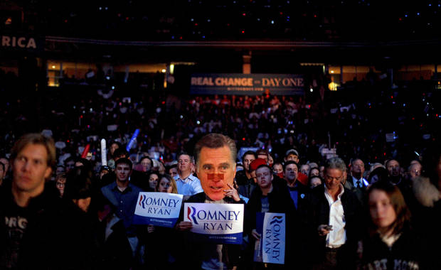 A supporter wearing a mask of Republican presidential candidate, former Massachusetts Gov. Mitt Romney, waits for Romney to take the stage at a campaign event at the Verizon Wireless Arena, Monday, Nov. 5, 2012, in Manchester, N.H. (AP Photo/David Goldman)