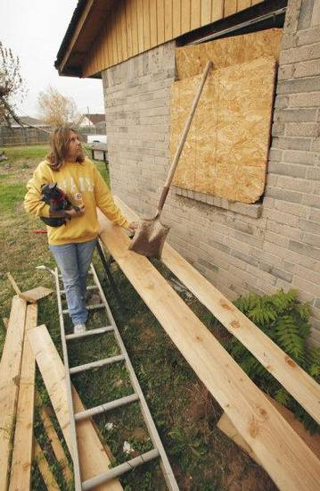 Linda McCanless props boards and leans a shovel against plywood to hold it over a missing window in the house where she and Kenneth Walker Jr. live Wednesday, Nov. 16, 2011, in Newcastle.  The room and most of his house is just as it was after being hit by a tornado May 24 <strong>STEVE SISNEY - THE OKLAHOMAN</strong>