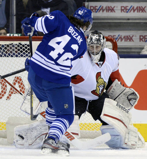 Toronto Maple Leafs centre Tyler Bozak (42) scores on Ottawa Senators goalie Ben Bishop during first-period NHL hockey game action in Toronto, Wednesday, March 6, 2013. (AP Photo/The Canadian Press, Frank Gunn)