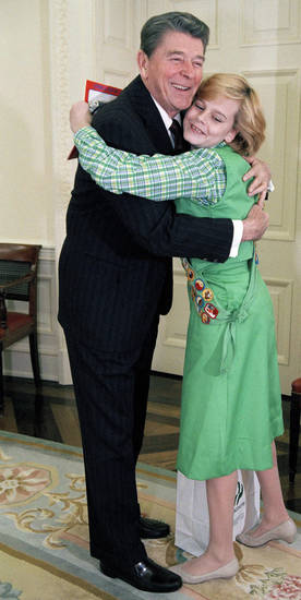 FILE - In this Jan. 9, 1986, file photo, President Ronald Reagan hugs Elizabeth Brinton, 14, of Falls Church, Va., during a meeting at the White House in Washington. Brinton who has held a Girl Scout cookie sales record for decades says she has no problem giving up her cookie crown to an Oklahoma girl who broke her record. Brinton set the one year sales record of 18,000 boxes as a teenager in the 1980s. She sold outside Metro stations in the Washington area and in 1986 even sold cookies to Reagan. Now a mother of two living in Alabama, Brinton says the new cookie queen, Katie Francis of Oklahoma City, called her to ask for advice. (AP Photo/Charles Tasnadi, File)