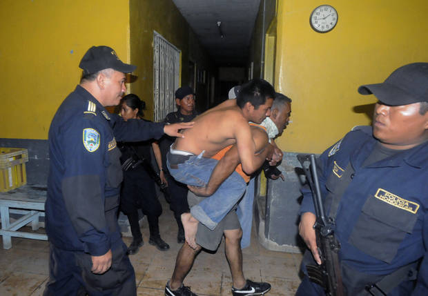 An injured inmate is carried away after a fire broke out at the prison in Comayagua, Honduras, a town 90 miles (140 kilometers) north of the Central American country's capital, Tegucigalpa, early Wednesday, Feb. 15, 2012. Radio reports from Comayagua said dozens of prisoners were burned beyond recognition and the prison was destroyed by the flames. The fire claimed the lives of at least 272 inmates. (AP Photo/Fernando Antonio)