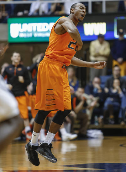 Oklahoma State's Markel Brown (22) celebrates after scoring during the first half of an NCAA college basketball game in Morgantown, W.Va., on Saturday, Feb. 23, 2013. (AP Photo/David Smith) ORG XMIT: WVDS103