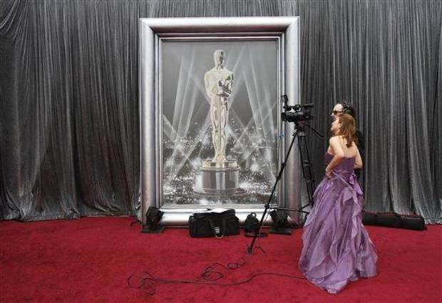 "Reporters from ""Cinema Today"" in Japan look over a shot as preparations continue for the 84th Academy Awards in Los Angeles on Sunday, Feb. 26, 2012.  The Oscars will be held later in the day."