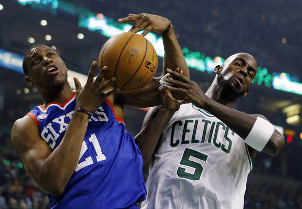 Philadelphia 76ers' Thaddeus Young (21) and Boston Celtics' Kevin Garnett (5) vie for a rebound in the first quarter of an NBA basketball game in Boston, Saturday, Dec. 8, 2012. (AP Photo/Michael Dwyer)