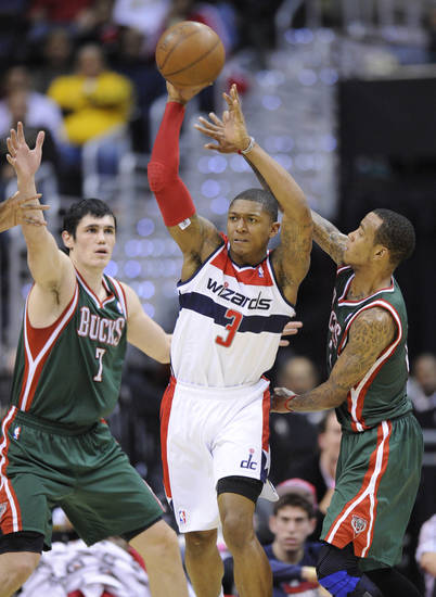 Washington Wizards guard Bradley Beal (3) tries to make a pass against Milwaukee Bucks forward Ersan Ilyasova (7), of Turkey, and Monta Ellis, right, during the first half of an NBA basketball game on Friday, Nov. 9, 2012, in Washington. (AP Photo/Nick Wass)