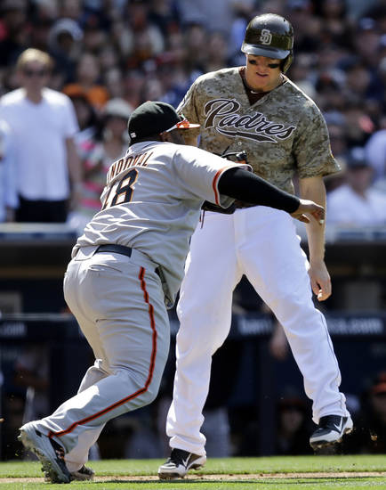 San Diego Padres' Nick Hundley is tagged out by San Francisco Giants third baseman Pablo Sandoval after being caught in a rundown while trying to score from third in the sixth inning of a baseball game in San Diego, Sunday, April 28, 2013. (AP photo/Lenny Ignelzi)