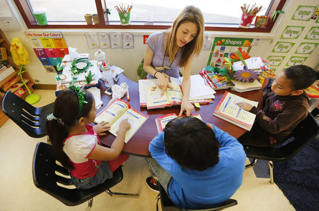 Cesar Chavez Elementary School teacher Lauren Nelson works with first-graders on a reading assignment at the school in southwest Oklahoma City.  PHOTO BY STEVE GOOCH, THE OKLAHOMAN