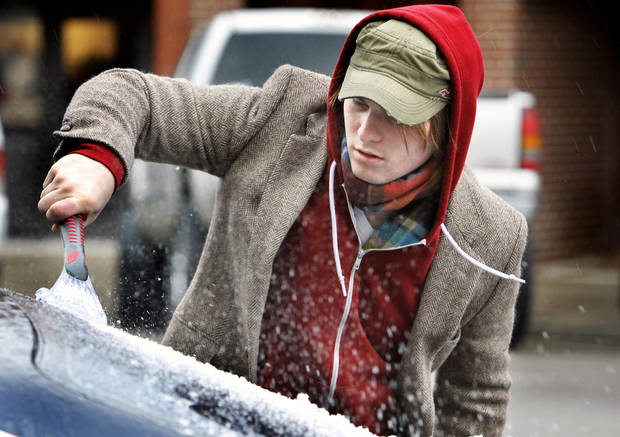 Joseph Rosser  of Oklahoma City clears ice from  his car windows Thursday as a winter storm moves into  Norman.  Photo by Steve Sisney, The Oklahoman