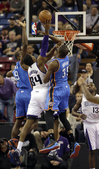 Sacramento Kings forward Jason Thompson, center, goes to the basket between Oklahoma City Thunder Serge Ibaka, of the Republic of Congo, left, and Kevin Durant during the first quarter of  an NBA basketball game in Sacramento, Calif., Friday, Jan. 25, 2013. (AP Photo/Rich Pedroncelli) ORG XMIT: SCA106