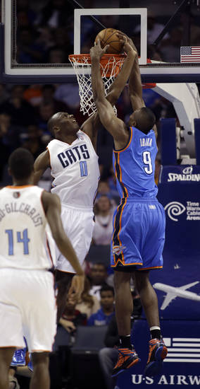 Charlotte Bobcats' Bismack Biyombo (0) tries for the block but misses as Oklahoma City Thunder's Serge Ibaka (9) dunks during the first half of an NBA basketball game in Charlotte, N.C., Friday, March 8, 2013. (AP Photo/Bob Leverone) ORG XMIT: NCBL103
