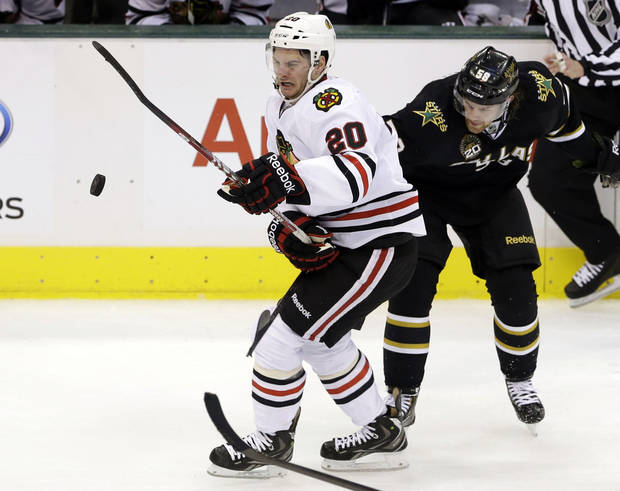 Chicago Blackhawks' Brandon Saad (20) attempts to control an airborne puck as Dallas Stars' Jordie Benn (58) defends in the second period of an NHL hockey game, Thursday, Jan. 24, 2013, in Dallas. (AP Photo/Tony Gutierrez)