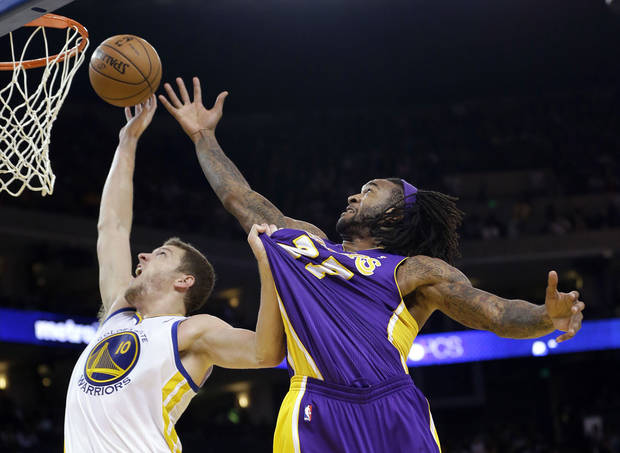 Golden State Warriors' David Lee (10) vies for a rebound against Los Angeles Lakers' Jodie Meeks (20) during the first half of an NBA basketball game in Oakland, Calif., Saturday, Dec. 22, 2012. (AP Photo/Marcio Jose Sanchez)