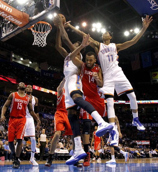Oklahoma City 's Hasheem Thabeet (34) an Jeremy Lamb (11) defend the basket over Houston's Daequan Cook (14) during the NBA basketball game between the Houston Rockets and the Oklahoma City Thunder at the Chesapeake Energy Arena on Wednesday, Nov. 28, 2012, in Oklahoma City, Okla.   Photo by Chris Landsberger, The Oklahoman