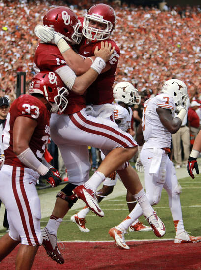 Oklahoma quarterback Blake Bell (10) celebrates his touchdown with teammate Brannon Green (82) as Trey Millard (33) looks on and Texas linebacker Demarco Cobbs (7) walks off during the first half of an NCAA college football game at the Cotton Bowl Saturday, Oct. 13, 2012, in Dallas. (AP Photo/Michael Mulvey)