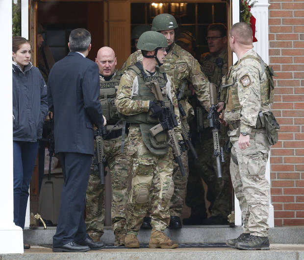 Officials exit St. Rose of Lima Roman Catholic Church while responding to a bomb threat, Sunday, Dec. 16, 2012, in Newtown, Conn. Worshippers hurriedly left the church Sunday, not far from where a gunman opened fire Friday inside the Sandy Hook Elementary School in Newtown. (AP Photo/Julio Cortez)