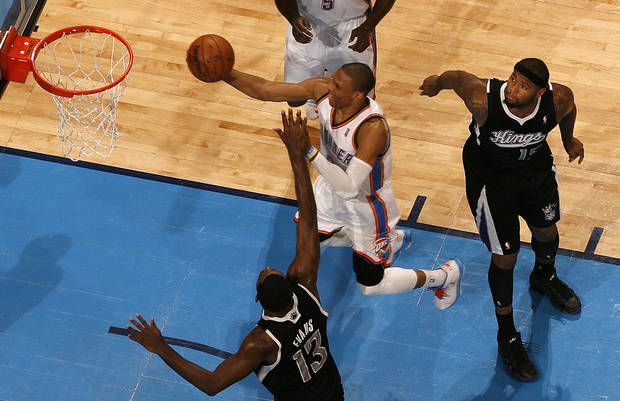 Oklahoma City's Russell Westbrook (0) goes to the basket between Sacramento's Tyreke Evans (13), and DeMarcus Cousins (15) during an NBA basketball game between the Oklahoma City Thunder and the Sacramento Kings at Chesapeake Energy Arena in Oklahoma City, Friday, Dec. 14, 2012. Photo by Bryan Terry, The Oklahoman
