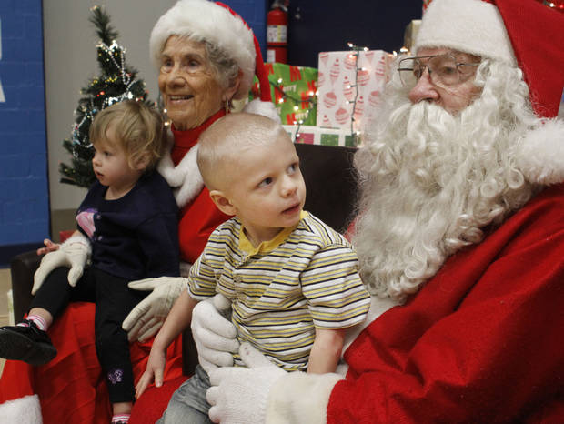 CHILD / KIDS: 22-month-old Destiny Johnson and Christopher Johnson, 3, sit on the laps of Santa and Mrs. Santa during the City Rescue Mission's annual Children's Christmas Party at the City Rescue Mission in Oklahoma City, OK, Thursday, December 20, 2012,  By Paul Hellstern, The Oklahoman