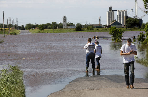 Matt Wyatt and Chase Biggs check the level of water flowing across Banner Road in El Reno as their friend, Tyler Eisenhour determines it is too deep and walks to their truck to find an alternate route to their work site on  Saturday, June 1, 2013.  Photo  by Jim Beckel, The Oklahoman.