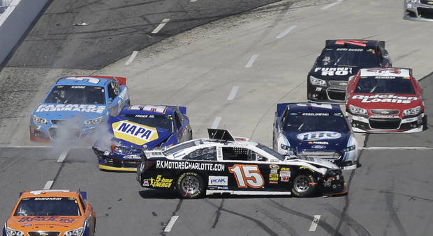 Clint Bowyer (15) spins out in front of Brad Keselowski (2) and Martin Truex Jr., (56) during the STP 500 NASCAR Sprint Cup series auto race at Martinsville Speedway in Martinsville, Va., Sunday April 7, 2013. (AP Photo/Steve Helber)