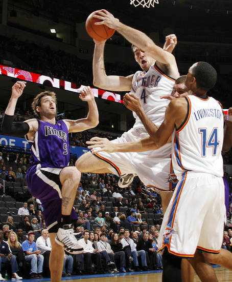 Oklahoma City's Nick Collison (4) grabs a rebound between Shaun Livingston (14), right, and Andres Nocioni (5) of Sacramento during the NBA preseason game between the Sacramento Kings and the Oklahoma City Thunder at the Ford Center in Oklahoma City, Thursday, Oct. 22, 2009. Photo by Nate Billings, The Oklahoman