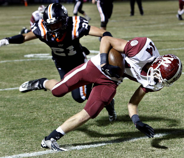 Wynnewood's Gus Reinert (14) keeps his balance and recovers to score on this pass play defended by Wayne's Charlie Garnder in high school Football on Friday, Oct. 26, 2012 in Wayne, Okla.  Photo by Steve Sisney, The Oklahoman