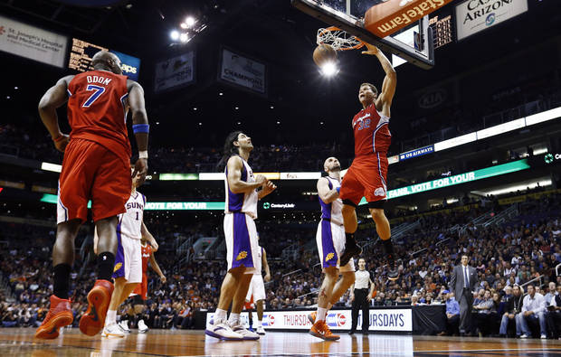 Los Angeles Clippers' Blake Griffin (32) dunks as Phoenix Suns' Marcin Gortat, second from right, of Poland, Luis Scola, of Argentina, and Clippers' Lamar Odom (7) watch during the first half of an NBA basketball game, Thursday, Jan. 24, 2013, in Phoenix. (AP Photo/Ross D. Franklin)