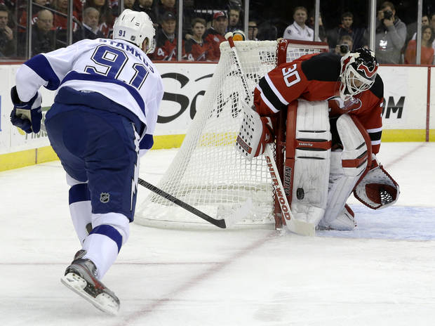 New Jersey Devils goalie Martin Brodeur (30) makes a save on a shot by Tampa Bay Lightning center Steven Stamkos (91) during the first period of an NHL hockey game, Thursday, Feb. 7, 2013, in Newark, N.J. (AP Photo/Julio Cortez)