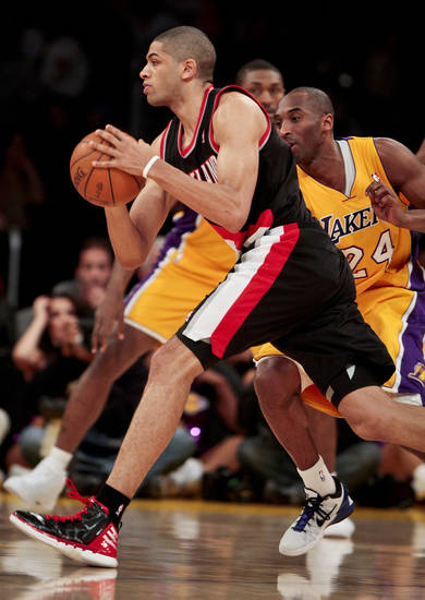 Portland Trail Blazers forward Nicolas Batum dribbles around Los Angeles Lakers guard Kobe Bryant during the first half on an NBA basketball game, Monday, Feb. 20, 2012, in Los Angeles. (AP Photo/Bret Hartman)