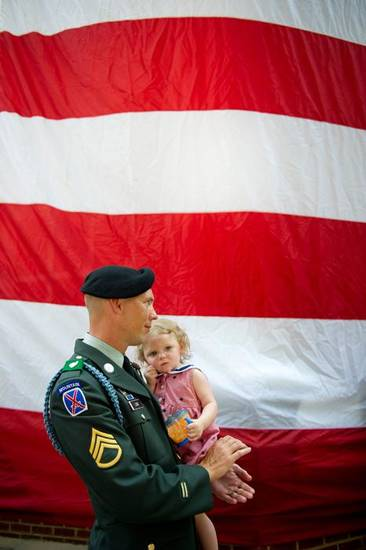 "Jacob Long, of the Georgia Army National Guard, holds his 14-month-old daughter, Charlotte, while listening to the song ""God Bless America"" during a Memorial Day ceremony, Monday, May 30, 2011, in Roswell, Ga. (AP Photo/Rich Addicks) ORG XMIT: GARA111"