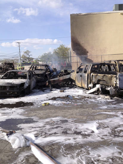 Burnt cars smolder in the parking lot where a Piper PA31 twin-engine crashed shortly after takeoff from Fort Lauderdale Executive Airport in Fort Lauderdale, Fla., Friday, March 15, 2013. All three aboard the plane were killed. No one on the ground was hurt. (AP Photo)