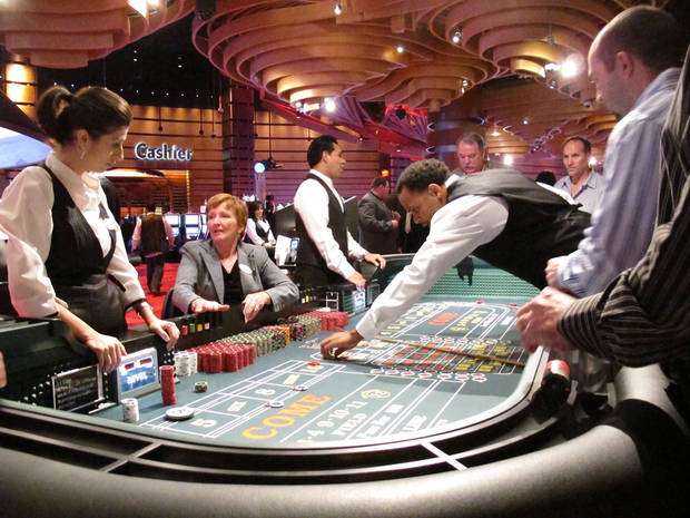 FILE - In this March 28, 2012 file photo, craps dealers help place bets for gamblers during a trial run at Revel, Atlantic City N.J.'s newest casino, which officially opened April 2. New Jersey lawmakers are expected to give final approval on Dec. 20, 2012 to a bill legalizing Internet gambling. It would authorize the casinos to offer online versions of all their normal games. The measure still needs Gov. Chris Christie's signature, which is far from certain. (AP Photo/Wayne Parry, File)