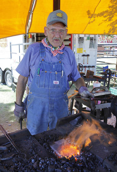 Bob McKelvain, from Sterling, cranks a hand forge at the Blacksmithing demonstration at the Oklahoma State Fair, Tuesday, September 18, 2012. McKelvain was making small spoons out of horseshoe nails. Photo By David McDaniel/The Oklahoman