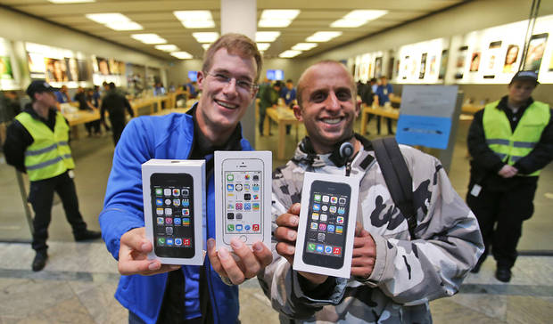 First customers of the Apple store in Oberhausen are all smile with their new iPhones in hand as they leave the store after the start of the new iPhone sale in Oberhausen, Germany, Friday, Sept. 20, 2013. (AP Photo/Frank Augstein)