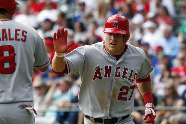 Los Angeles Angels' Mike Trout (27) high-fives Kendrys Morales (8) after scoring on a single by Albert Pujols during the third inning of the first baseball game of a doubleheader, Sunday, Sept. 30, 2012, in Arlington, Texas. The Angels won 5-4. (AP Photo/LM Otero)