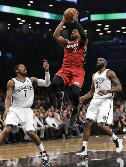 Miami Heat guard Dwyane Wade (3) goes up for a layup, between Brooklyn Nets guard Joe Johnson (7) and forward Reggie Evans (30) during the first half of on NBA basketball game Wednesday, Jan. 30, 2013, in New York. (AP Photo/Kathy Willens)