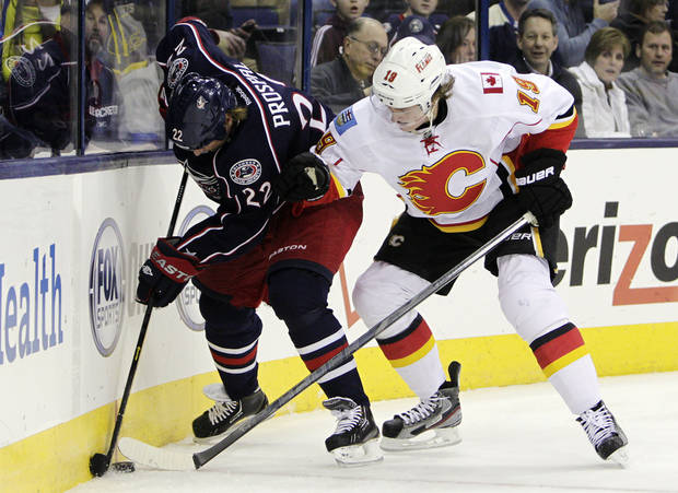 Columbus Blue Jackets' Vinny Prospal (22), of the Czech Republic, keeps the puck away from Calgary Flames' Blair Jones during the second period of an NHL hockey game, Thursday, Feb. 7, 2013, in Columbus, Ohio. (AP Photo/Jay LaPrete)