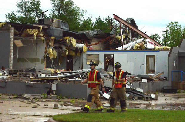 Two Norman firefighters walk by a building on North Jones Avenue that was damaged by a tornado that hit, Friday afternoon April 13, 2013 in Norman, Okla. (AP Photo/The Norman Transcript, Kyle Phillips)