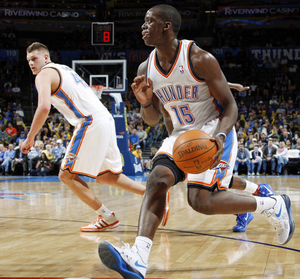 Oklahoma City's Reggie Jackson (15) dribbles the ball near Cole Aldrich (45) during the NBA basketball game between the Detroit Pistons and Oklahoma City Thunder at the Chesapeake Energy Arena in Oklahoma City, Monday, Jan. 23, 2012. Oklahoma City won, 99-79. Photo by Nate Billings, The Oklahoman