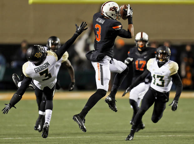 Oklahoma State's Marcell Ateman (3) makes a catch between Baylor's Demetri Goodson (3) and Terrell Burt (13) in the first quarter during a college football game between the Oklahoma State University Cowboys (OSU) and the Baylor University Bears (BU) at Boone Pickens Stadium in Stillwater, Okla., Saturday, Nov. 23, 2013. Photo by Nate Billings, The Oklahoman